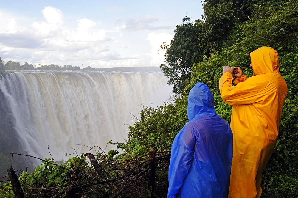 Tourists in rain jackets photographing the Victoria Falls, waterfall on the Zimbabwean side of the river Zambezi, Victoria Falls town, Zimbabwe, Africa