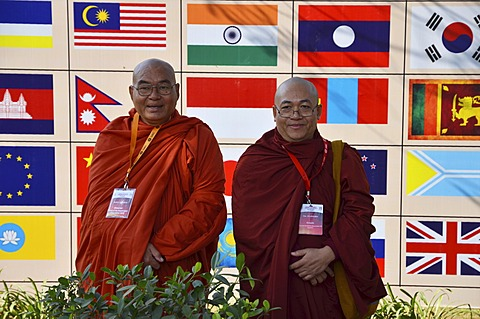 Two monks with red and orange robes, participants of the Global Buddhist Congregation 2011, Buddhist dignitaries from various Buddhist traditions and schools are photographed in front of national flags in Nehru Park, Gandhi Smitri, New Delhi, India, Asia