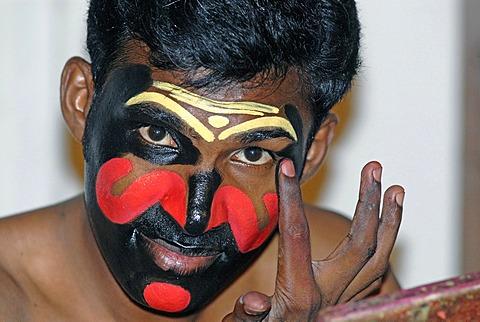 Applying the make-up for the power-hungry Kathakali character Chuvanna Thaadi, Kathakali dance theatre, Kochi, Kerala, South India, India, Asia