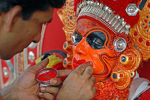 Painting the face of a Theyyam performer, preparing for a ritual, near Kasargod, North Kerala, South India, Asia