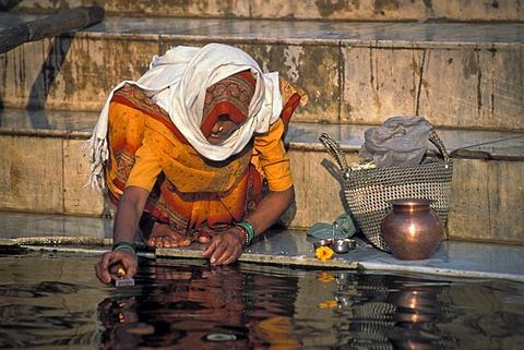 Woman during a morning prayer or puja, putting oil lamp on the Ganges River, ghats, Kashi, Varanasi or Benares, Uttar Pradesh, North India, India, Asia