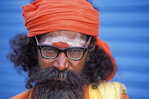 Sadhu wearing glasses in front of a blue wall, portrait, Ramanathaswami Temple, Rameshwaram or Ramesvaram, Tamil Nadu, South India, India, Asia