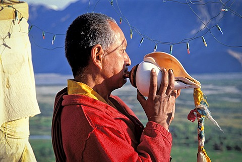 Monk blowing conch shell, Deskit or Diskit Monastery, Gompa, Hunder, Nubra Valley, Ladakh, Indian Himalayas, Jammu and Kashmir, North India, India, Asia - 832-372425
