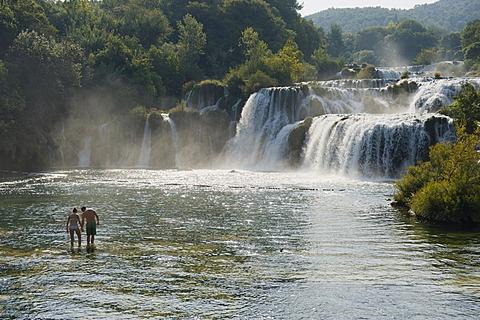 Couple standing in front of waterfalls in Krka National Park, Skradin, Sibenik-Knin, Dalmatia, Croatia, Europe