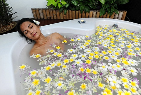 Woman in a sea of flowers in the tub, spa - 832-372540