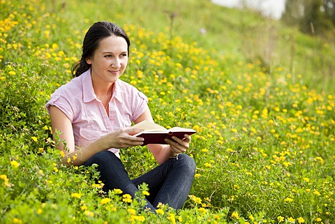 Young woman sitting on a meadow, reading a book