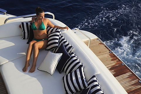 Young woman wearing a green bikini sitting on the rear deck of a motor yacht, French Riviera, Cote d'Azur, Mediterranean Sea, Europe - 832-372572