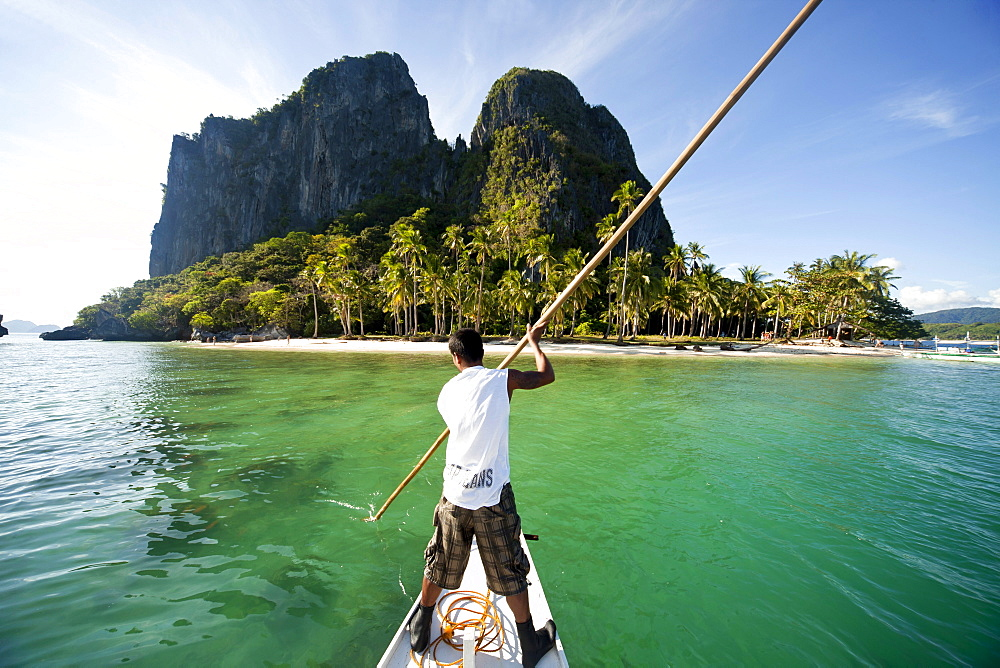 Boatsman in a traditional outrigger boat approaching Inabuyutan Island, Bacuit Archipelago, El Nido, Palawan, Philippines, Asia