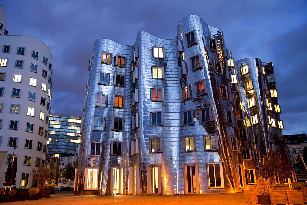 A building by American architect Frank O. Gehry at night, Neuer Zollhof building complex, Medienhafen district, Duesseldorf, North Rhine-Westphalia, Germany, Europe