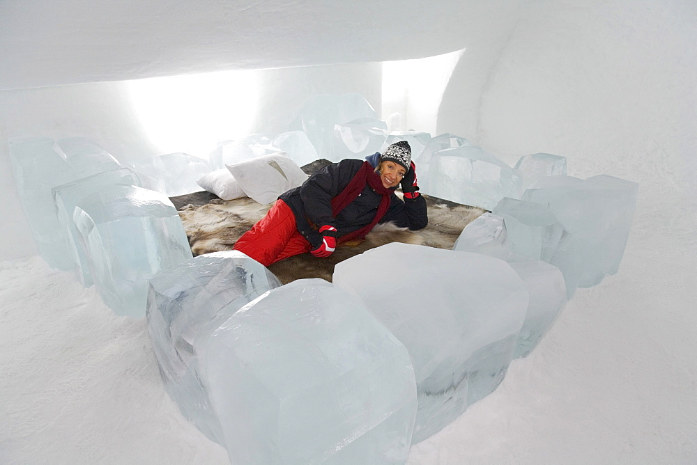Tourist lying on a bed in a hotel room of the ice hotel in Jukkasjaervi, Lappland, Northern Sweden