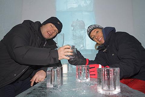 Ice bar of the ice hotel of Jukkasjaervi, woman and man clinking ice glasses, Jukkasjaervi, Lappland, Northern Sweden - 832-372810