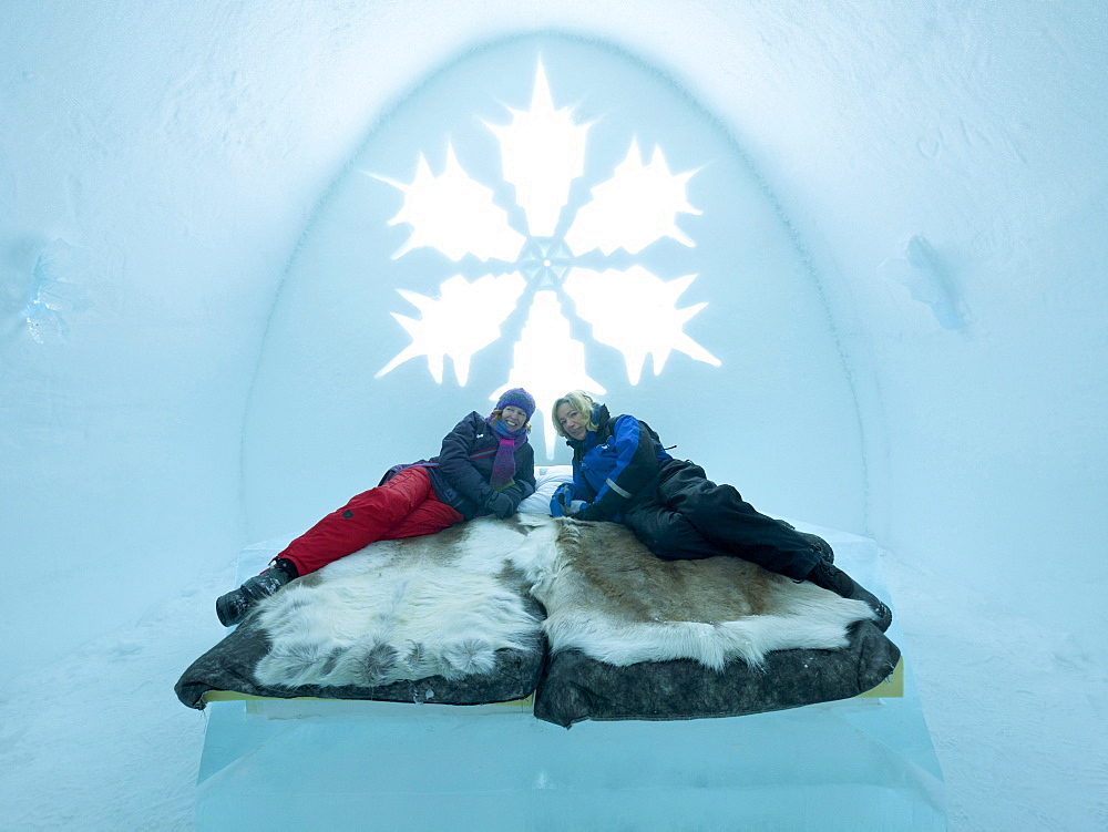Two tourists lying on a bed in a bedroom in the ice hotel in Jukkasjaervi, Kiruna, Lappland, northern Sweden, Sweden, Europe