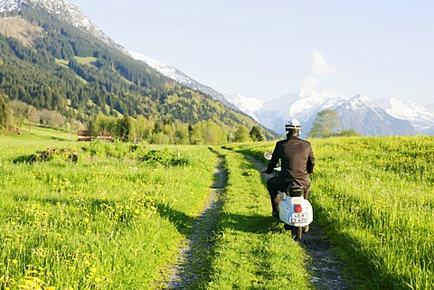 Businessman, 29, on a classic motor scooter, Allgaeu, Bavaria, Germany, Europe