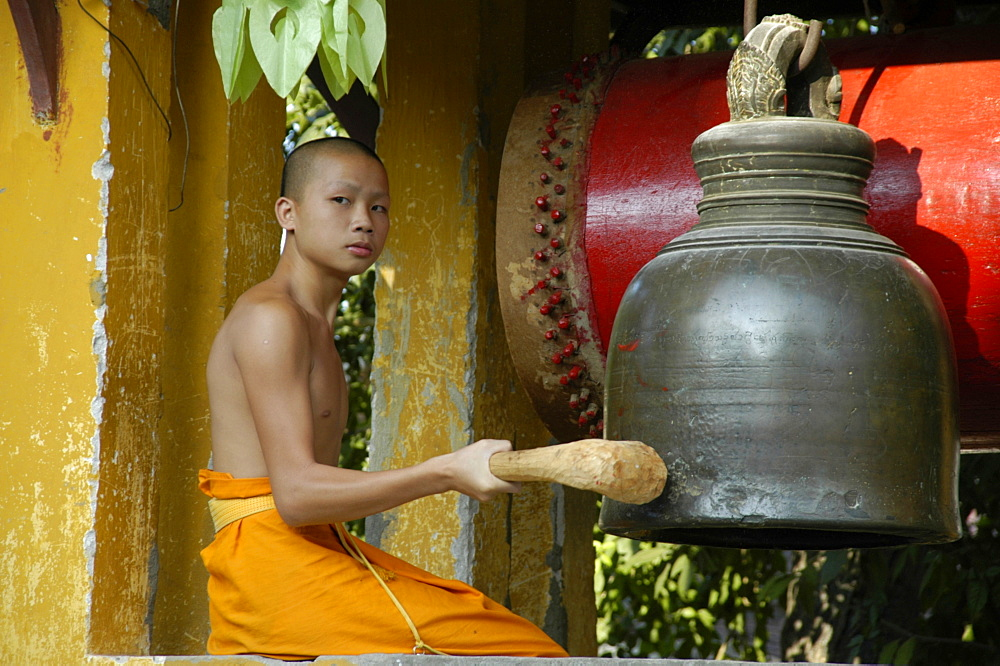 Young buddhist monk ringing the bell, Wat Sirimungkhun, Luang Prabang, Laos, Southeast Asia