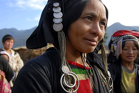 Portrait, smiling woman of the Phixor Akha ethnic group, traditional clothing dyed with indigo, headdress with silver coins, village Ban Bounpiang, Boun Neua district, Phongsali province, Laos, Southeast Asia, Asia