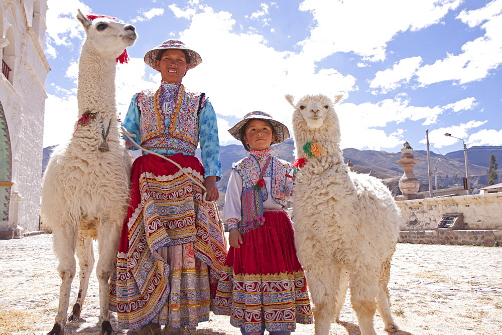Woman and girl with llama and alpaca in Maca near Colca Canyon, Peru, South America