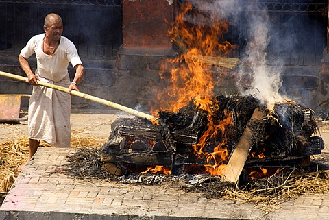 Traditional funeral, untouchable priest of the lowest caste tending pyre, Pashupatinath, Nepal, Asia