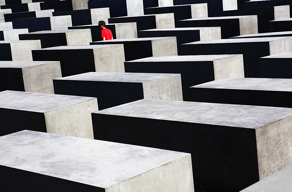 Lone person among concrete slabs at the Holocaust Memorial (Memorial to the Murdered Jews of Europe), Berlin, Germany