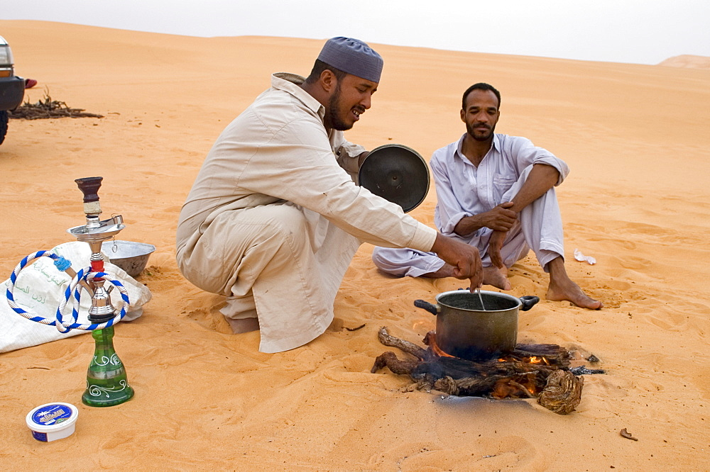 Libyan beduins sitting in the sand cooking their meal, Libya