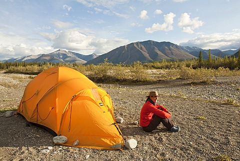 Young woman relaxing, enjoying evening light, sitting beside her tent, Northern Mackenzie Mountains behind, Wind River, Yukon Territory, Canada