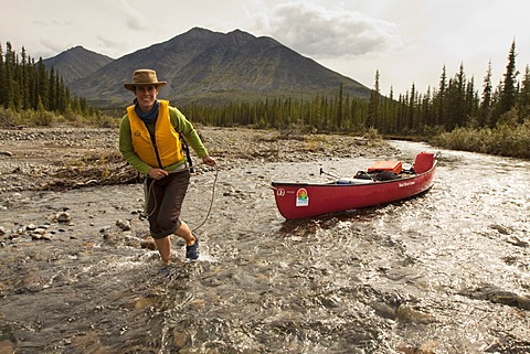 Young woman lining, wading, pushing, pulling a canoe in shallow water, Wind River, Peel Watershed, Northern Mackenzie Mountains behind, Yukon Territory, Canada