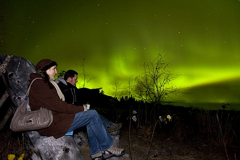Couple, woman and man, sitting in a wooden chair, watching swirling Northern lights, Polar Aurorae, Aurora Borealis, green, near Whitehorse, Yukon Territory, Canada