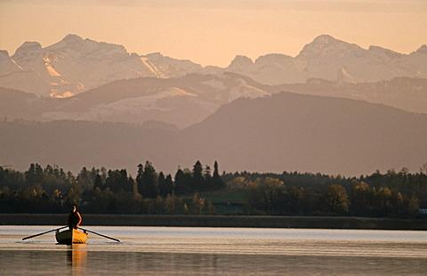 Fisherman on Lake Pfaeffikon in front of the Alps, Switzerland, Europe