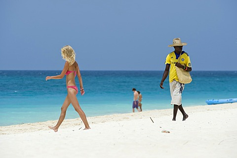 Souvenir seller and female holidaymaker on the beach of Kendwa Rocks, north coast of Zanzibar, Tanzania, Africa