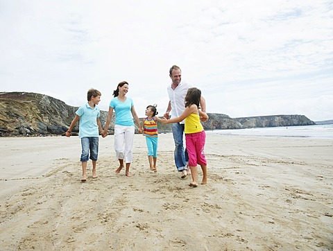 Woman, man, two girls and a boy walking along the beach, hand in hand, laughing, Bretagne, France, Europe