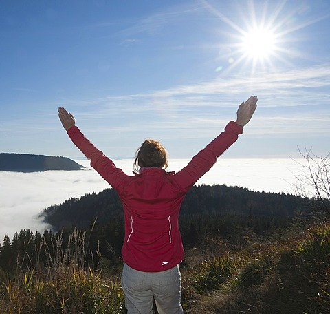 Woman hiker with outstretched arms looking at a fog shrouded valley, Black Forest, Baden-Wuerttemberg, Germany, Europe