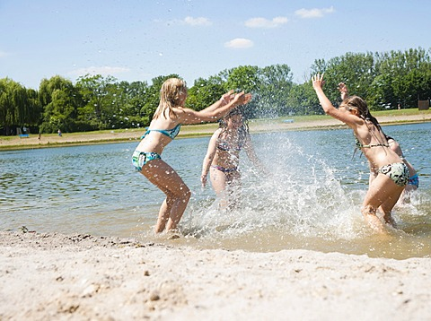 Group of girls splashing each other and playing in a lake