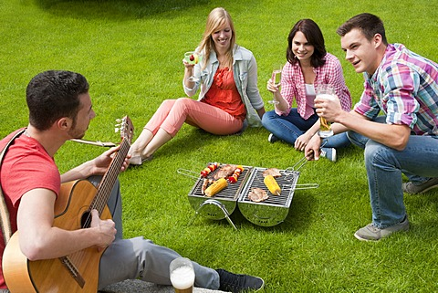 Group of young people having a barbecue in the garden