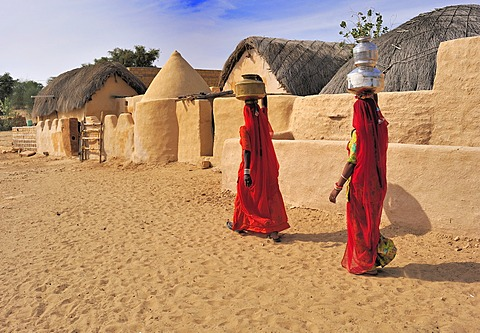 Two Indian women wearing red saris carrying water filled jugs on their heads through a village, Thar Desert, Rajasthan, India, Asia