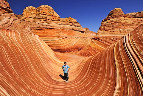 Tourist in The Wave, banded eroded Navajo sandstone rocks with Liesegang Bands, Liesegangen Rings, or Liesegang Rings, North Coyote Buttes, Paria Canyon, Vermillion Cliffs National Monument, Arizona, Utah, USA
