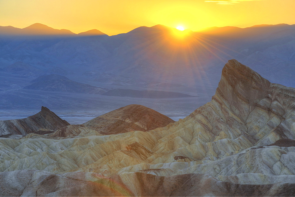 View from Zabriskie Point or Zabriske Point, eroded rocks discoloured by minerals, Manly Beacon, sunset, Panamint Range at back, Death Valley National Park, Mojave Desert, California, USA