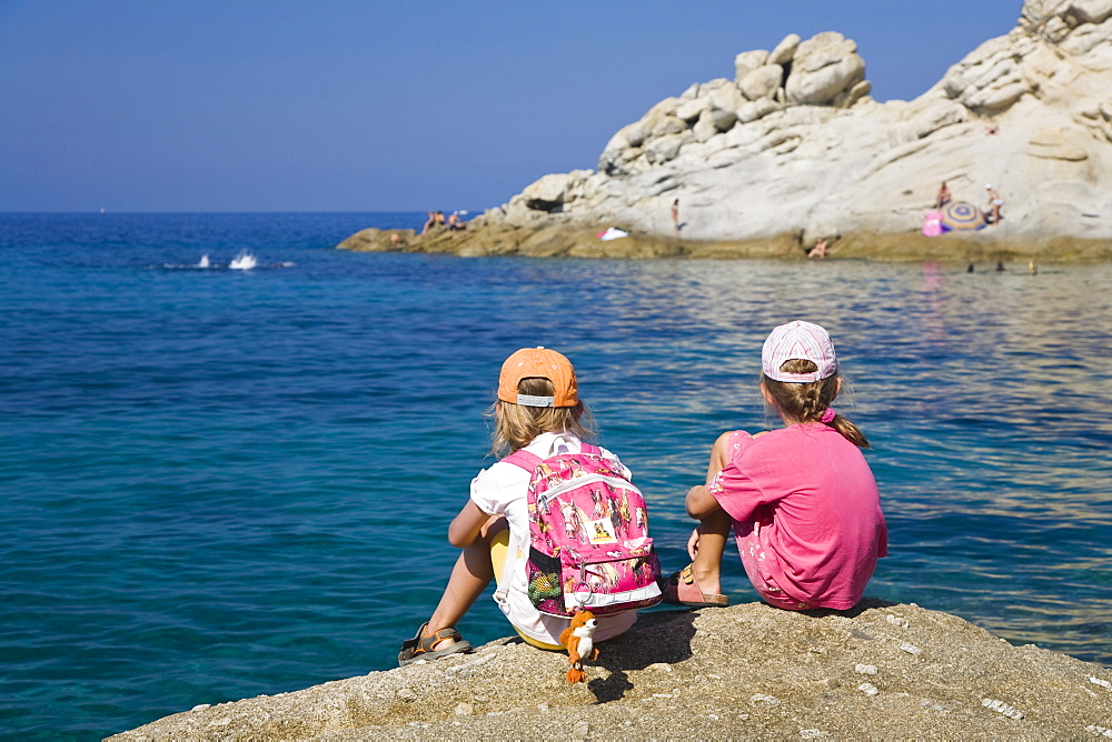 Two girls sitting on a cliff near Sant\'Andrea, Elba, Tuscany, Italy, Mediterranean, Europe