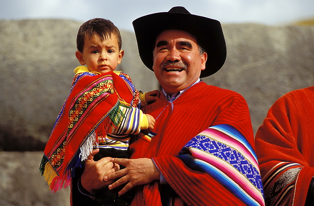 Man with child on his arm . father and son in typical clothes , Suedamerika, Peru, Anden