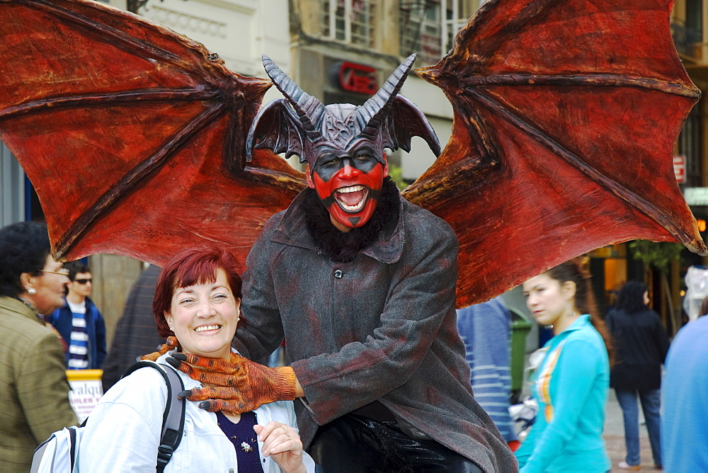 Man wearing a Lucifer costume strangling a smiling woman, crude carnival characters and satirical sculptures at a parade, Fallas festival, Falles festival in Valencia in early spring, Spain, Europe