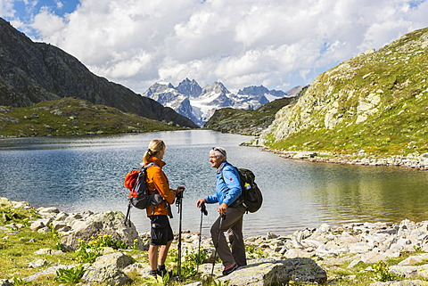 Hikers, Macun Lakeland, Verstancla Group at the back, Swiss National Park, Graubünden, Switzerland, Europe