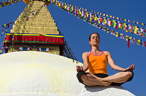 Young woman practicing yoga at Boudnanath stupa, showing the Padmasana pose, or Lotus pose, Kathmandu Valley, Kathmandu, Kathmandu District, Bagmati Zone, Nepal, Asia
