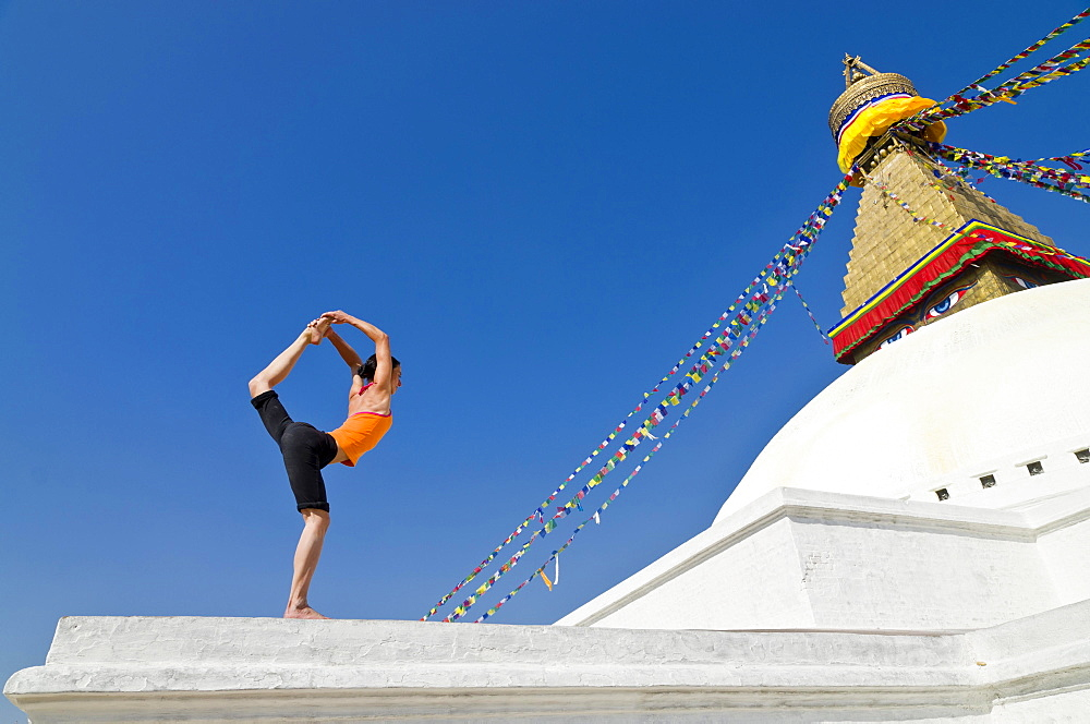Young woman practicing yoga at Boudnanath stupa, showing the Natarajasana pose, or Lord Shiva's pose, Kathmandu Valley, Kathmandu, Kathmandu District, Bagmati Zone, Nepal, Asia
