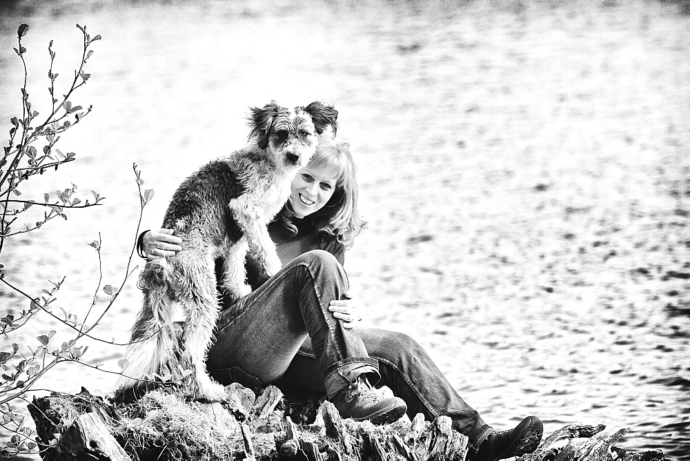 Woman sitting with her dog on a rock by a lake