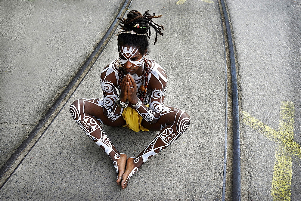 Young man with Polynesian war paint, prayer pose, sitting on a street with tracks, Berlin, Germany, Europe