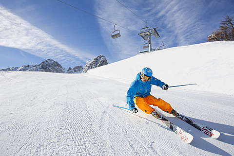 Skier with a helmet skiing down a slope, Mutterer Alm near Innsbruck, Tyrol, Austria, Europe - 832-378650
