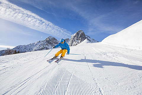 Skier with a helmet skiing down a slope, Mutterer Alm near Innsbruck, Tyrol, Austria, Europe