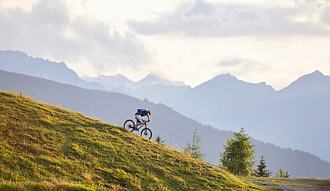 Mountain biker on the descent on a fire road, Mutterer Alm near Innsbruck, Northern chain of the Alps behind, Tyrol, Austria, Europe - 832-378655