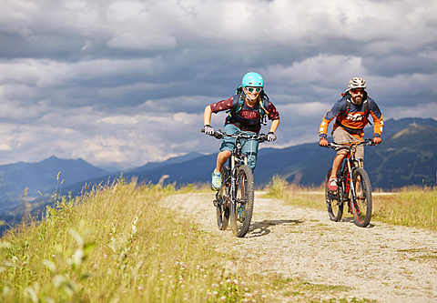 Two mountain bikers with helmets riding on gravel roads, Mutterer Alm near Innsbruck, Patscherkofel, Tyrol, Austria, Europe