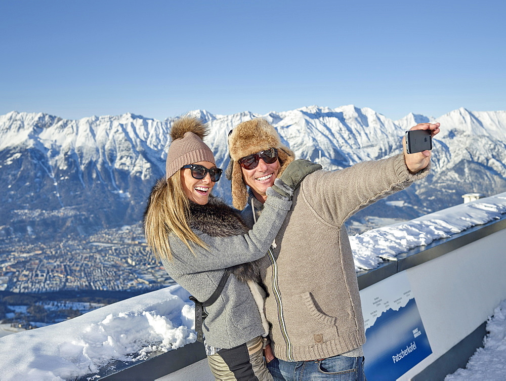 Couple photographing, making a selfie in front of mountain scenery, Patscherkofel, Patsch, Inntal chain, Innsbruck, Tyrol, Austria, Europe - 832-378664