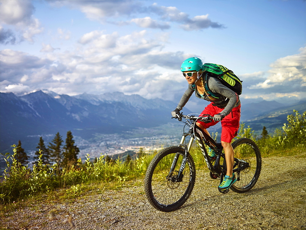 Mountain biker with a helmet riding on a gravel road, Mutterer Alm near Innsbruck, Northern chain of the Alps behind, Tyrol, Austria, Europe
