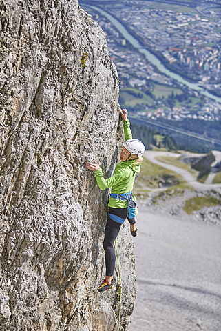 Climber with helmet climbing on a rock wall, behind Innsbruck, Northern Alps, Innsbruck, Tyrol, Austria, Europe